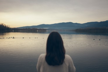 Back view of woman looking the lake.