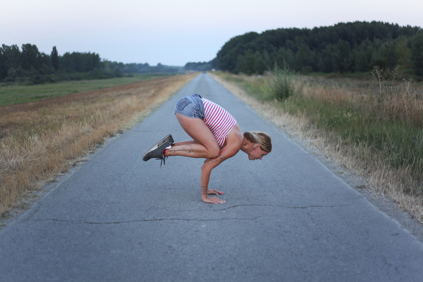 Woman practice yoga on an empty road