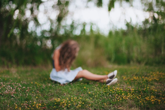 Teen girl feeling depressed crying on a meadow